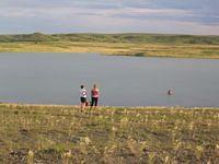 Jesica and Krystal at Ft. Peck Lake.  Jason (Red) is in the water with the dogs.